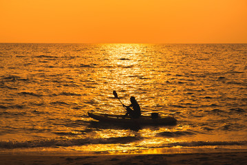 fisherman are boating on sea in sunset
