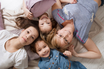 Happy loving family.  Mother with little daughters  having fun in children room.
