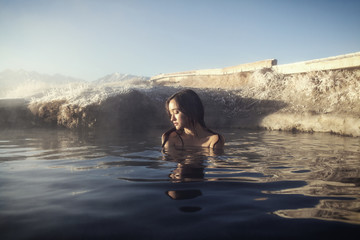 Mid-adult woman relaxing in hot spring