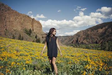 Young woman standing in field against mountain