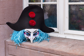 Basel carnival. Schnabelgasse, Basel, Switzerland - March 7, 2017. Closeup of a single carnival mask with blue hair and black hat resting on the window sill outside of a restaurant.
