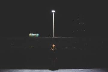 Young beautiful caucasian woman in the night under lamppost illuminated