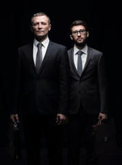 Two serious businessmen  isolated on black background looking in