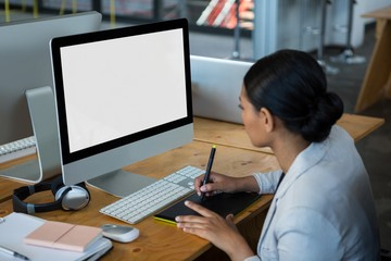 Female graphic designer using graphics tablet at desk