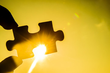 hand trying to connect couple puzzle piece with sunset background. Jigsaw alone wooden puzzle against sun rays. one part of whole. symbol of association and connection. business strategy.