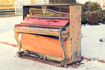 old piano painted in colorful colors is standing on snow