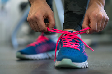 Running shoes - woman tying shoe laces. Woman getting ready for engage in the gym