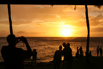 Silhoutte of a man taking a families photo with the sunset in the background, others enjoying the sunset