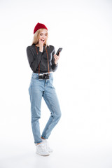 Young excited woman photographer looking at mobile phone