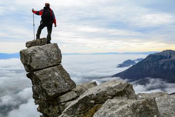 kayalıklarda sisli manzara izleyen dağcı
