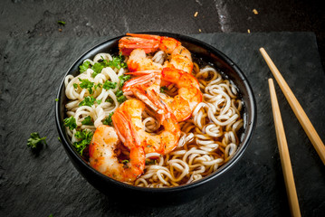 Asian soup with noodles (ramen), with miso paste, soy sauce, greens and shrimps prawn. On a black stone table, with chopsticks. Copy space