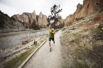 Young man running on footpath by river against mountain