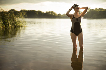 Woman in swimming costume standing in pond