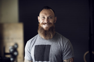 Portrait of smiling man with beard in gym