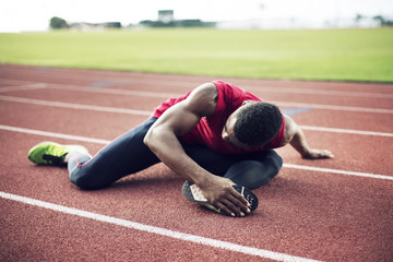 Sportsman sitting on running track and stretching