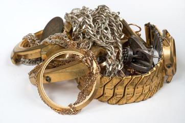 Scrap of precious metals. Old and broken jewelry, watches of gold and silver on a white background. Selective focus.