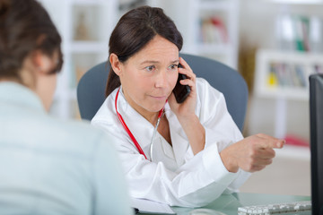 doctor with patient talking on the phone and showing results