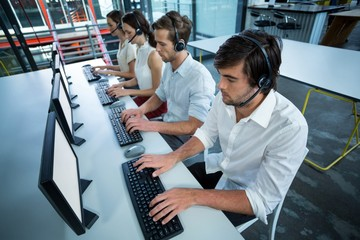 Business executives with headsets using computer