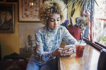Young woman using mobile phone in cafe,