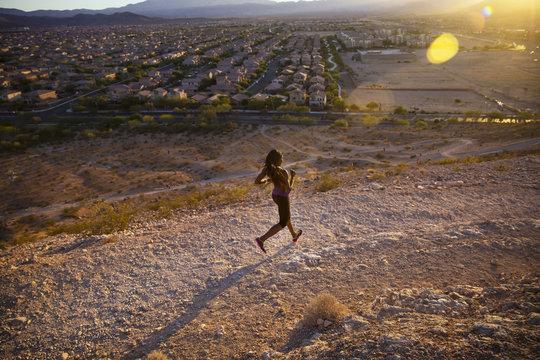 Woman jogging along dirt road,