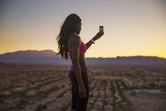 Young woman photographing suburb,