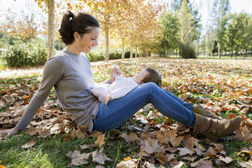 Woman playing with baby girl in park