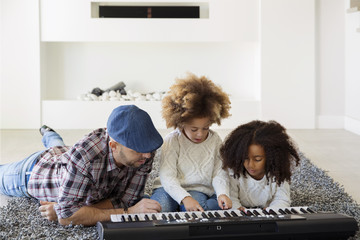 Two girls playing keyboard synthesizer with father