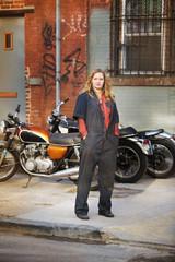 Female mechanic next to motorcycles