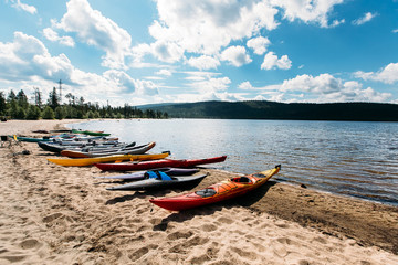 Kayaks of a boat stand on a sandy beach, the sun. Summer.