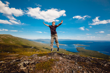 Male tourist man sitting jumping on a mountain on a white sea background. Kandalaksha, Murmansk region, the Kola Peninsula, Russia.