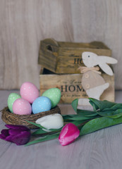 Easter eggs in nest on wooden background. Tulips, wooden baskets and wooden bunny.