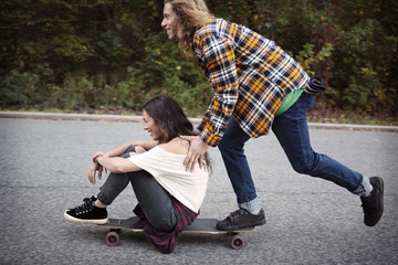 Young couple on skateboard in park