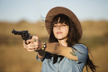 Young woman aiming with revolver