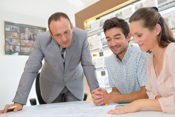 Estate agent looking at plans with young couple