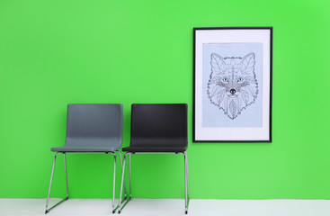 Modern chairs near green wall with abstract painting