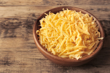 Bowl with grated cheese on wooden background