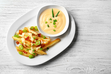 Plate with tasty cheese fries and sauce on white wooden table