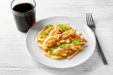 Plate with tasty cheese fries, sauce and glass of soda water on white wooden table