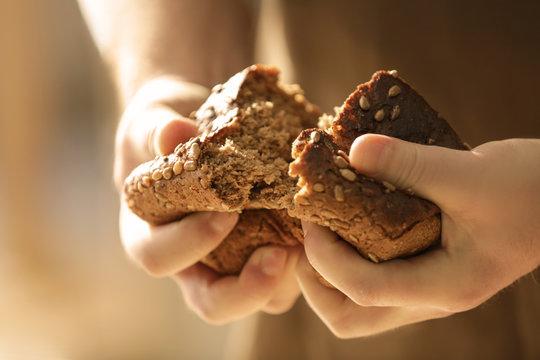 Man breaking off piece of bread, closeup