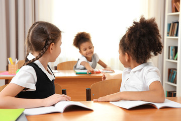 Beautiful elementary schoolgirls studying in classroom