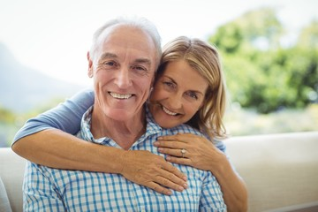 Portrait of smiling senior woman embracing a man in living room