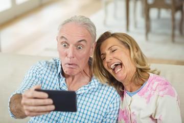 Senior couple taking a selfie on mobile phone in living room