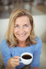Smiling senior woman having cup of coffee in living room