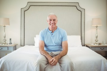 Portrait of smiling senior man sitting on bed in bedroom