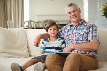 Portrait of grandfather with her grandson holding book on sofa