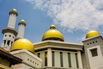 the gold dome of a mosque with cloudy sky as background photo taken Pekalongan Indonesia