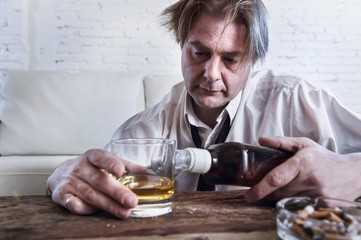 depressed alcoholic businessman with loose necktie wasted and drunk drinking whiskey