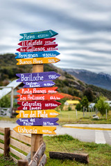 Colorful direction and city sign post in El Chalten, Argentina with Patagonia mountains in background