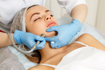 Dermabrasion cheekbones girl. Machine cosmetology. Spa. Facial Rejuvenation. Mechanical peeling skin.