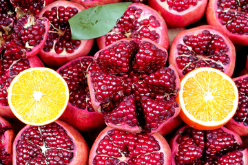 Sliced orange on background of sliced pomegranates close up